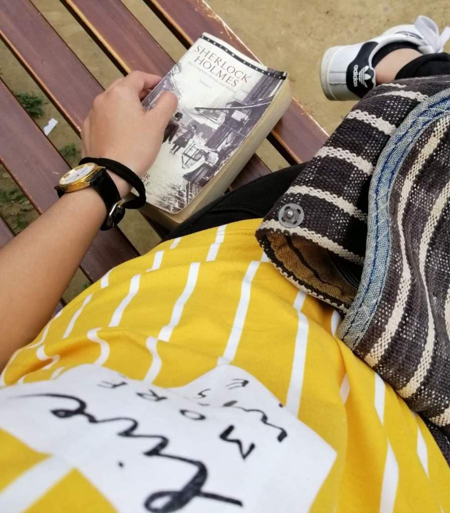 a girl wearing yellow sitting on a bench with a Sherlock Holmes book