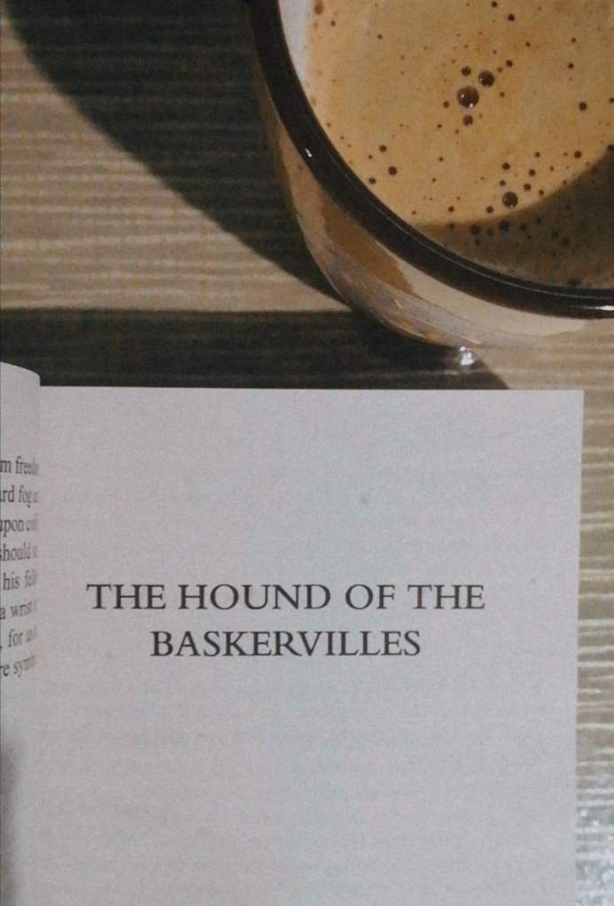 A book titled The Hound of Baskervilles by Sir Arthur Conan Doyle on a table with a cup of coffee